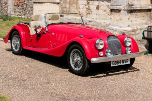 Framlinghan, England - July 10, 2015: Red replica of a Morgan veteran sports car with the hood down outside a church in Framlingham, Suffolk,