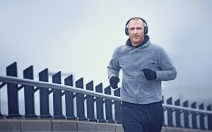 Middle aged man jogging in the city in winter listening to music on his wireless headphones